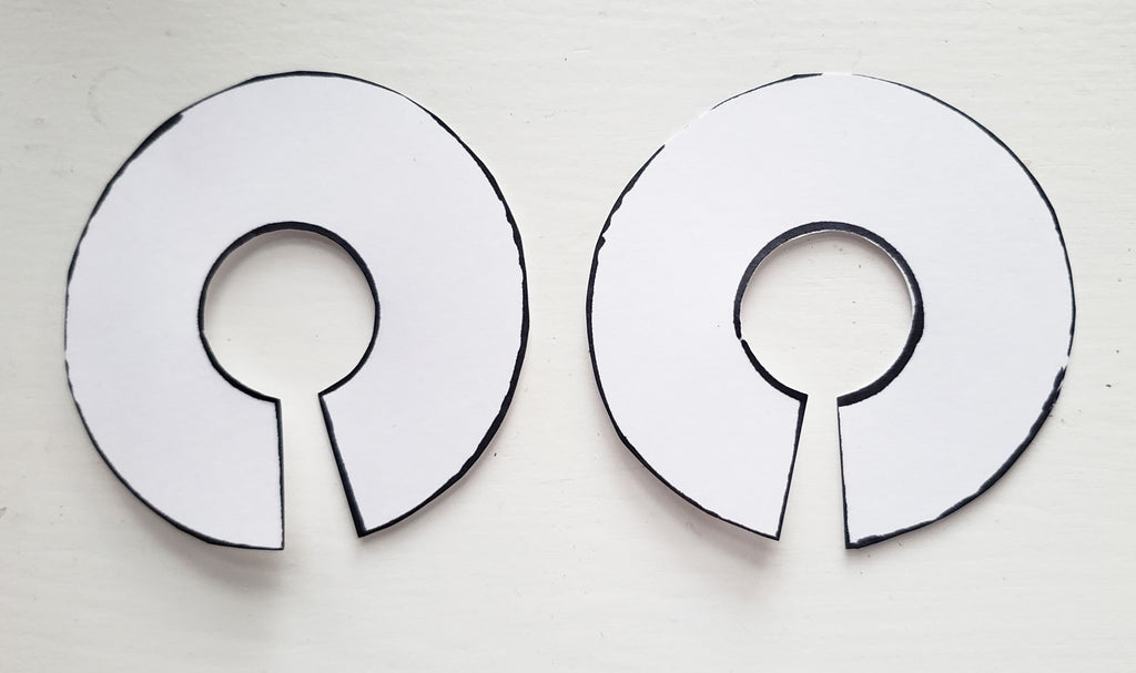 Two paper circles cut out with a slit through to the centre
