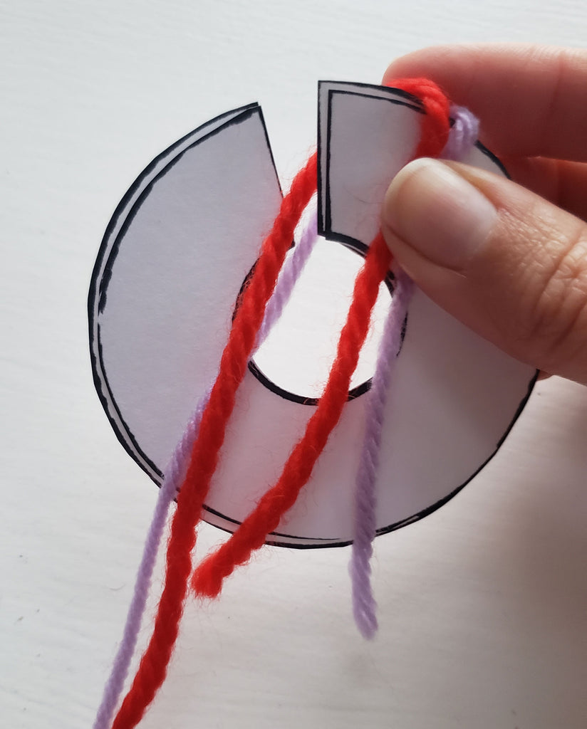 Red and purple yarn is being wrapped around a pom pom disk