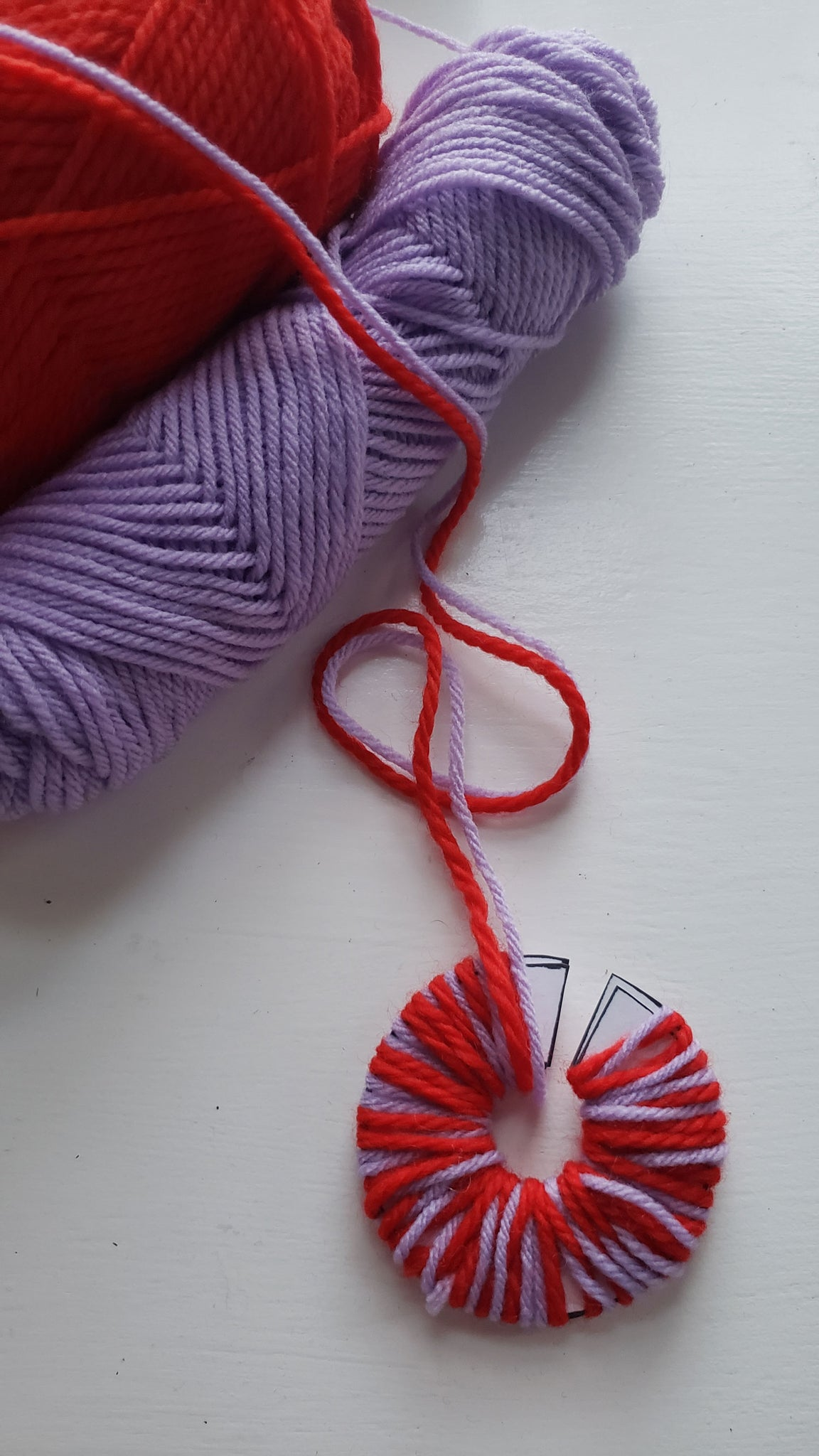 Red and purple yarn is being wrapped around a circular disk