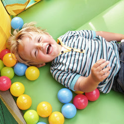 Young boy lying on his back in bouncy castle playing  with balls