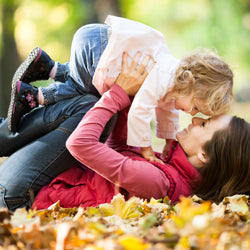 Mother and daughter playing outdoors in autumn setting