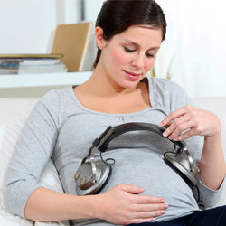 Pregnant woman holding  headphones on her belly music for baby