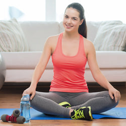 Pregnant woman in sports gear  sitting on mat at home training in front of couch