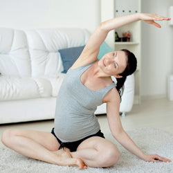 Pregnant woman performs yoga poise  at home in her living room