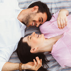 Pregnant woman lying  on bed with her partner looking at each other