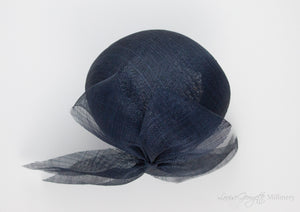 Top view. Luxurious Pinokpok hat with navy straw bow placed on a timeless Beret shape. Hat suitable for Royal Ascot, Epsom races, Weddings, and other special occasion outfits. Handmade Millinery made in London.