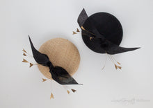 Two straw hat variations of the hayley hat. Hat features a bow on pillbox hat with feather spray.