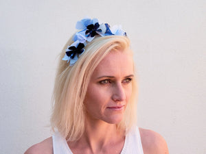 Blonde model wearing Sylvie headband in blue, white and navy metallic flowers. Handmade Millinery made in London.