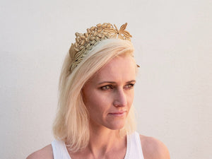 Blonde model wearing gold Lacey headband. Handmade Millinery made in London.
