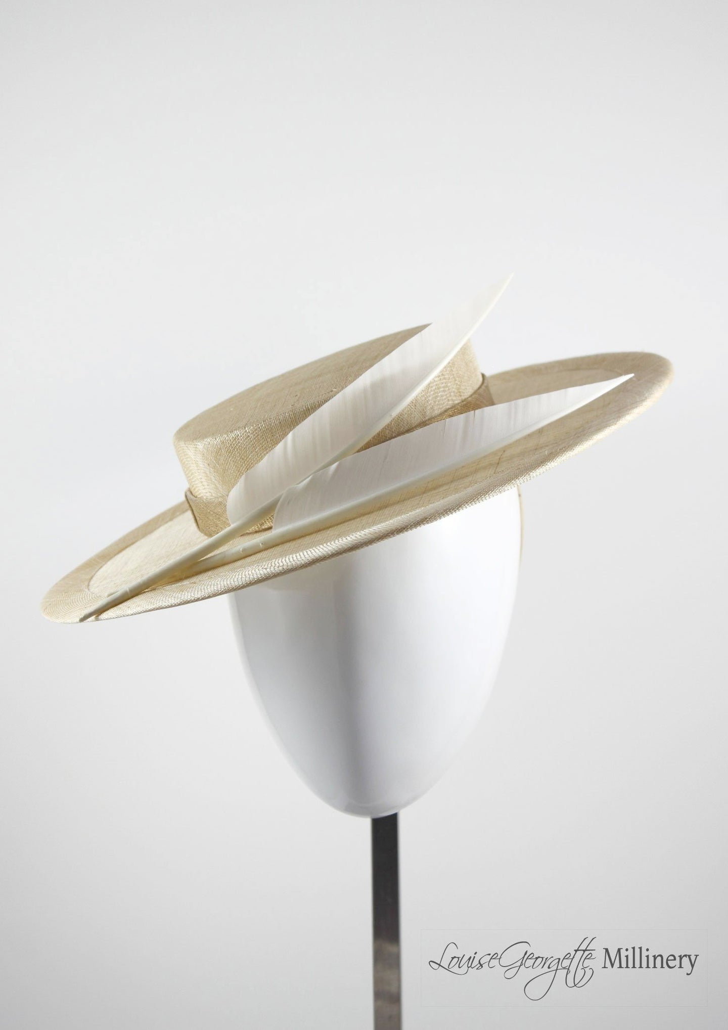 Natural coloured straw boater hat with two cream feathers. Handmade London Millinery. Front view.