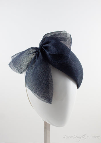 Side view. Luxurious Pinokpok hat with navy straw bow placed on a timeless Beret shape. Hat suitable for Royal Ascot, Epsom races, Weddings, and other special occasion outfits. Handmade Millinery made in London.