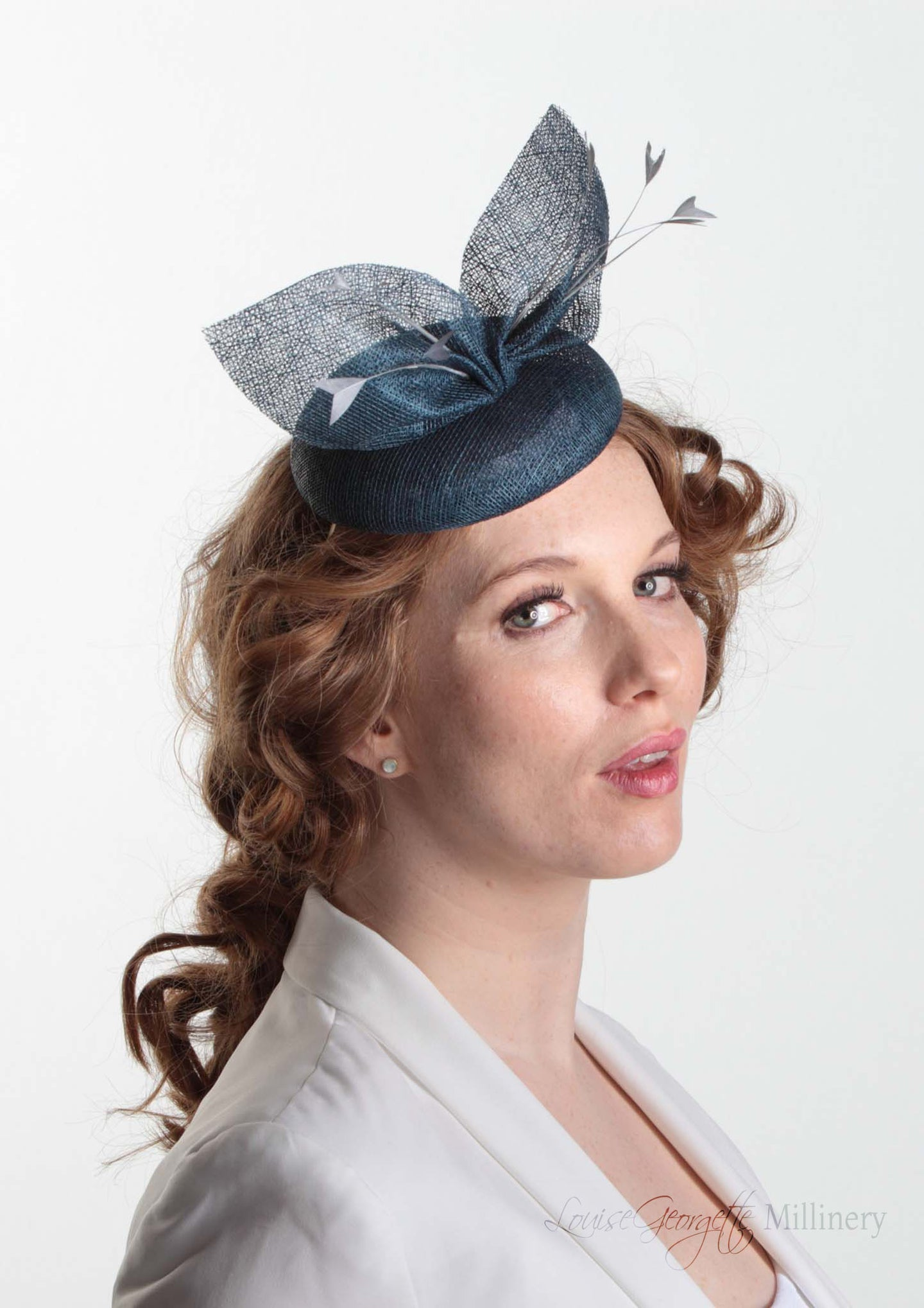 Royal Blue straw bow hat with feathers. Royal enclosure approved. Millinery handmade in London. Louise Georgette Millinery. Model side view.