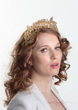 Lacey tiara style gold  crown on headband. Model side view. Millinery handmade in London.
