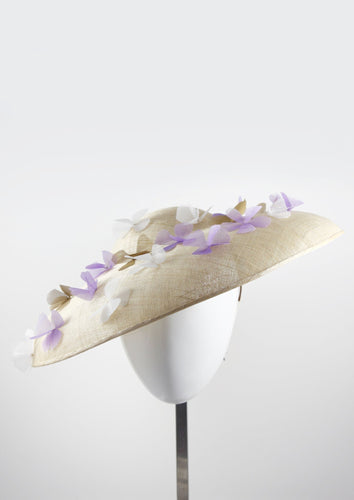 Wide brimmed disc hat with lilac and white flowers. Front view. Handmade in London.