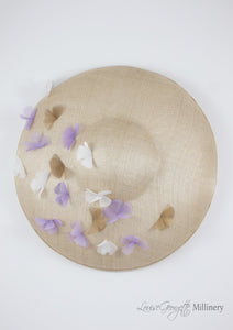 Wide brimmed disc hat with lilac and white flowers. Top view. Handmade in London.