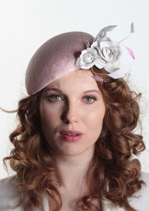 Pink sinamay Beret with white handmade leather flower. Front view of model. Handmade Millinery made in London.