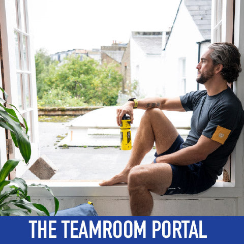 man looking out of a window wearing Crewroom Team Clothing