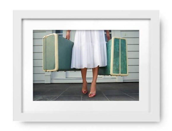 Woman Leaving Entrace Door Carrying Two Suitcases by Noel Hendrickson, Photos.com by Getty Images