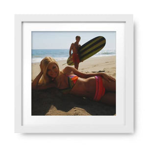 Young Woman Lying on Beach with Man Holding Surfboard in Background, by Tom Kelley Archive, Photos.com by Getty Images