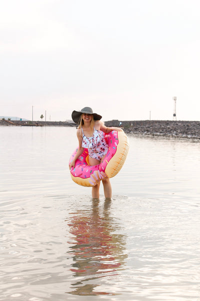 Blonde girl standing ankle deep in lake wearing a floral one piece swimsuit and a donut floaty