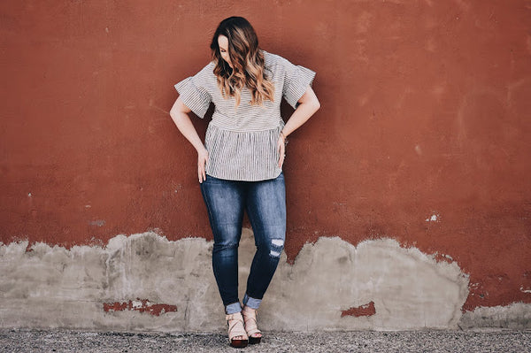 Bailey against a red wall wearing a striped peplum top with ruffle sleeves from Indigo Lane, a modest clothing boutique