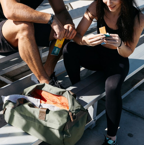 Two people in working out clothing, sitting down eating Rise Bars