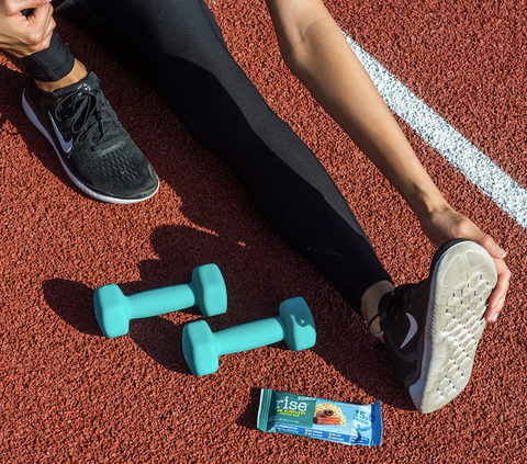 Person stretching on track next to weights and a Sunflower Cinnamon Rise Bar