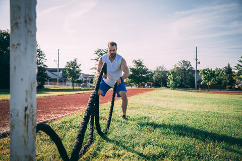 Man exercising with ropes outside