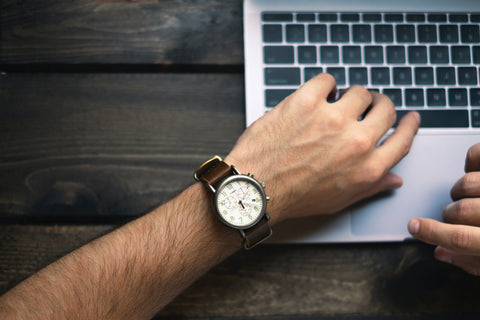 Man with watch at laptop