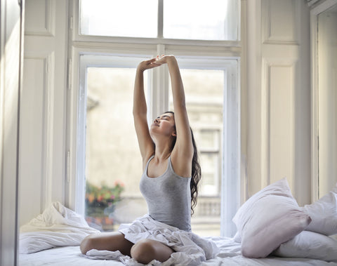 Woman stretching in bed, tips for better sleep quality