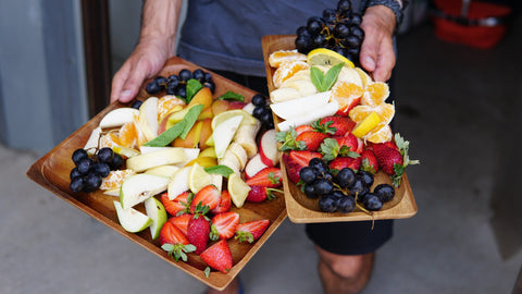 Person carrying trays of fruits