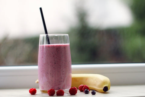 Healthy smoothie with fruits next to it
