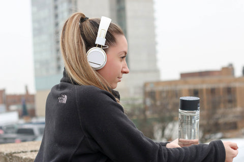 Woman outside exercising with headphones on and a water bottle