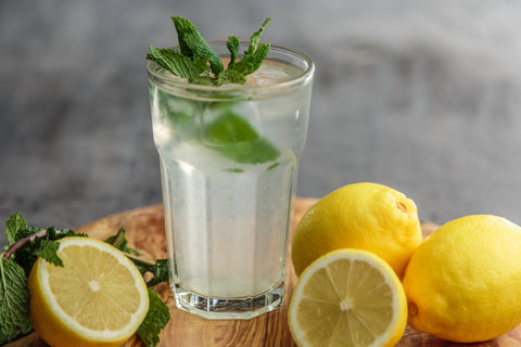 Glass of lemon water with water and mints around it