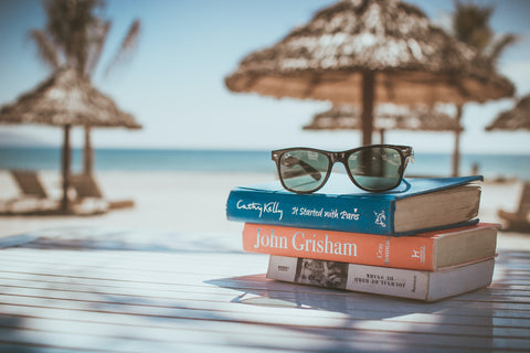 Sunglasses on stack of books at tropical location