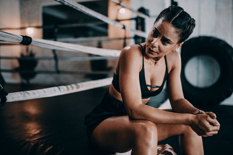 Woman resting by sitting on boxing ring after workout