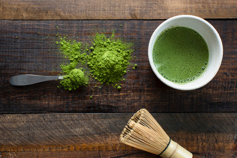Cup of matcha tea, matcha powder, and wooden whisk