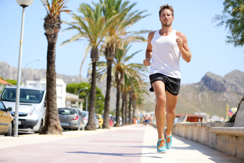 Fit male runner running outside on boardwalk. Young man model tr