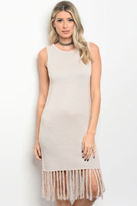sleeveless chunky knit sweater dress that features a rounded neckline and fringe trim