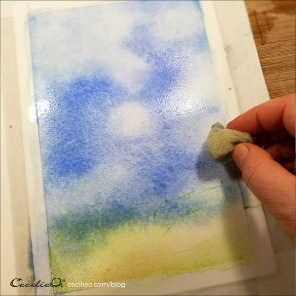 Blotting out white clouds with a watercolor sponge