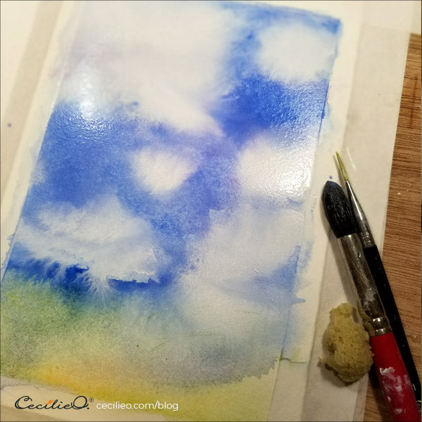 Diluting the edges of the white gouache clouds with water