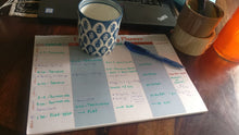 Label Shabel weekly  family planner on desktop with coffee mug and schedule written