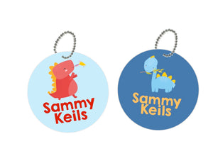 pair or round metal bag tags for kids in light and dark blue with cute dinosaurs