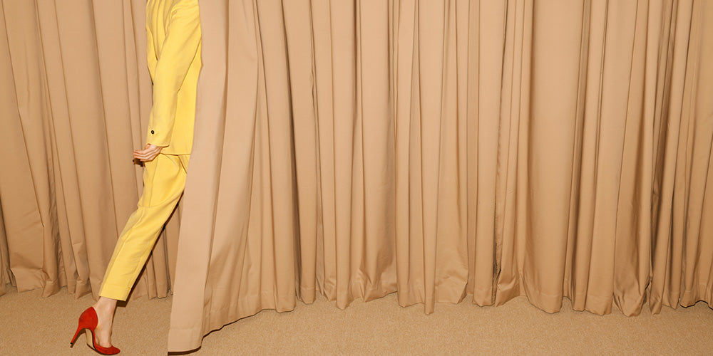 lady in yellow suit walking behind curtain
