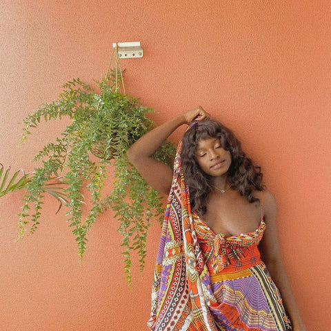 Black woman leaning on an orange wall with her eyes closed, wearing a colour dress and Ayune hair ethical hair extensions