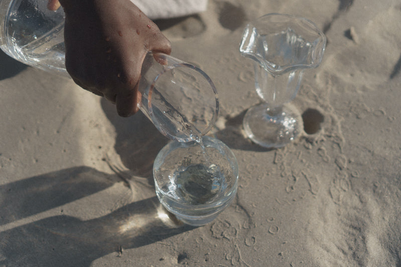 Black woman pour water in to two glass cups on the beach.