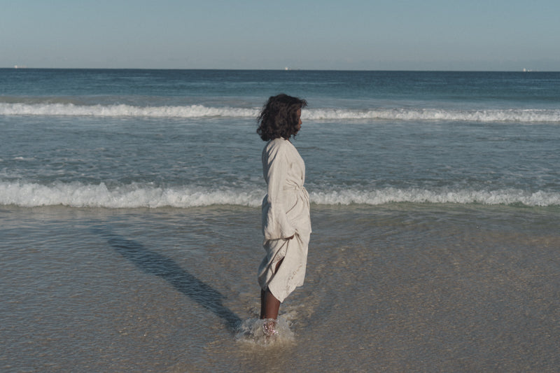 Black woman standing in front of the ocean. She is standing side-ways and looking away from the camera.