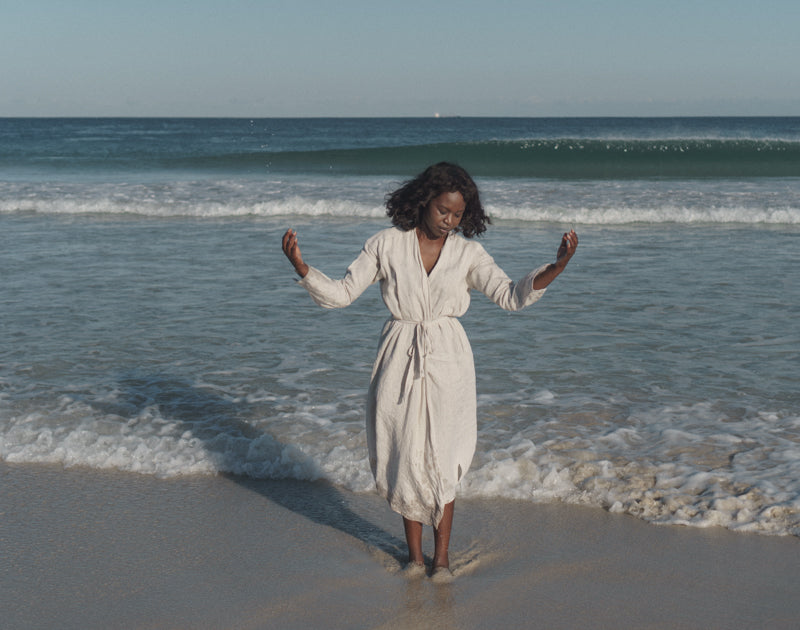 Black woman standing in front of the ocean on the sand. She is looking down and away from the camera.