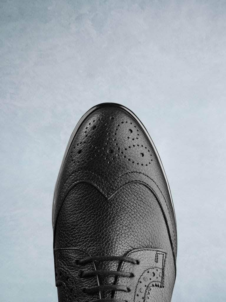 Featuring a brogue detailed elegant black leather almond toe.