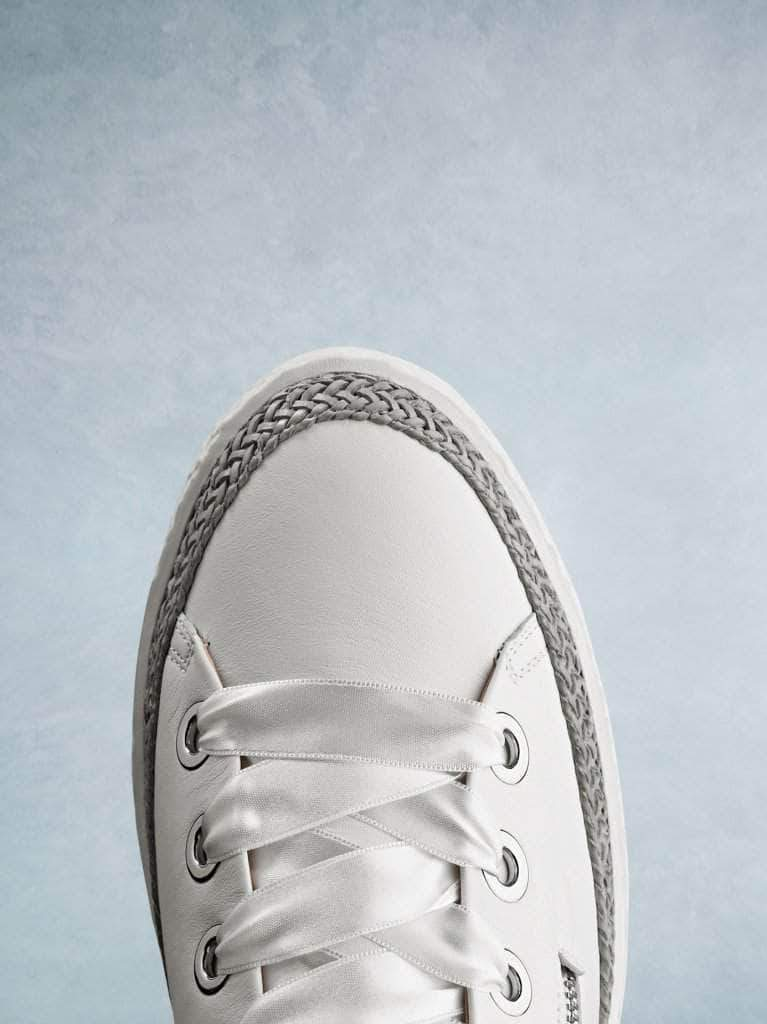 This white leather trainer has a smooth round toe highlighted by the lace trim.